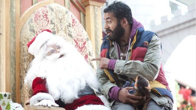 A Very Harold & Kumar 3D Christmas - Movie Still: Kal Penn w Santa - H - 2011