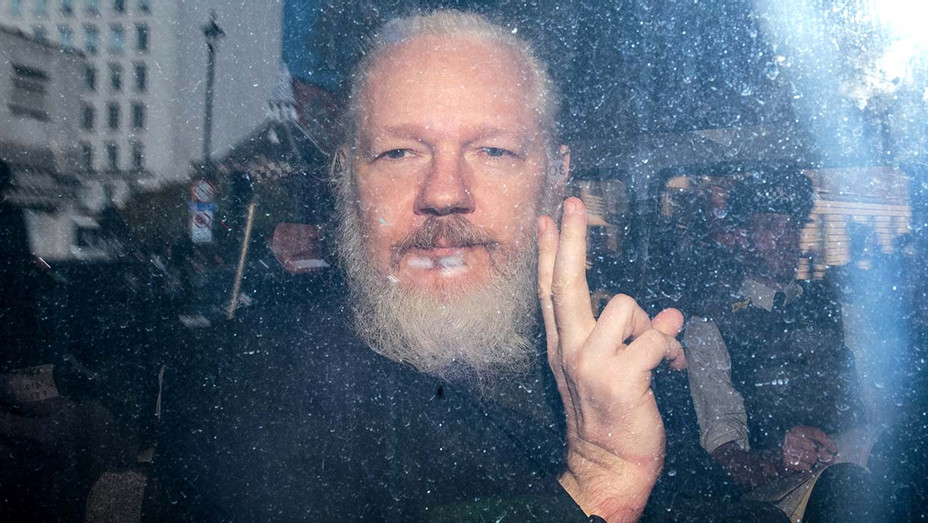 Julian Assange gestures to the media from a police vehicle on his arrival at Westminster Magistrates court on April 11, 2019 - Getty-H 2019