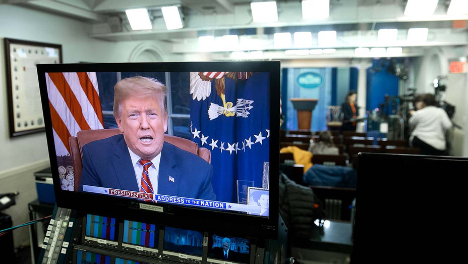 US President Donald Trump appears on a television screen - Getty - H 2019