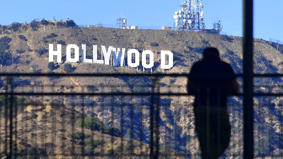 A man views the Hollywood sign from a walkway at a Hollywood shopping mall - Getty - H 2019