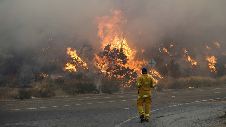 ONE TIME USE ONLY -A member of the news media watches flames from a wildfire along Sierra Highway Thursday, Oct. 24, 2019, in Santa Clarita, Calif- AP -H 2019
