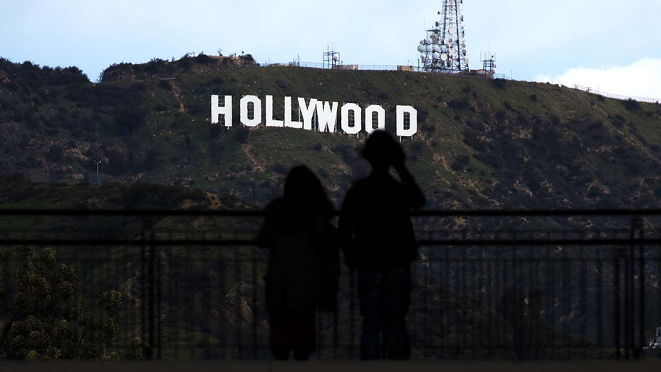 Two tourists look at the Hollywood sign - Getty - H 2019