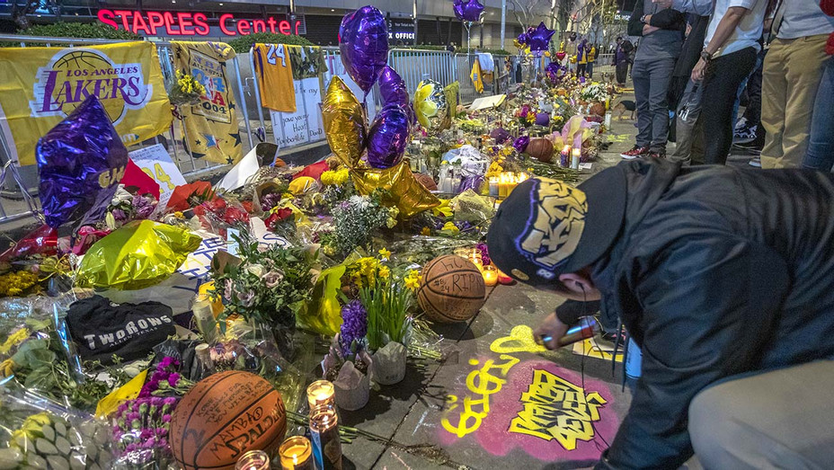 A man spray paints a memorial tribute near Staples Center before the first Lakers game since former NBA star Kobe Bryant - Getty - H 2020