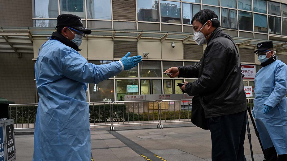 Security guards wearing protective clothes control an access point to Huashan Hospital in Shanghai - Getty - H 2020