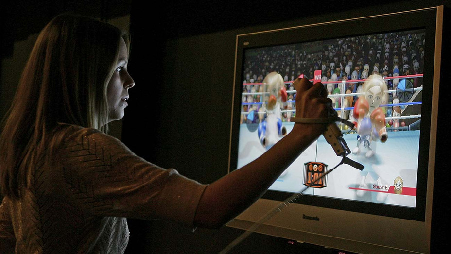 A woman uses a wireless controller to play a boxing game on a Nintendo Wii - Getty - H 2020