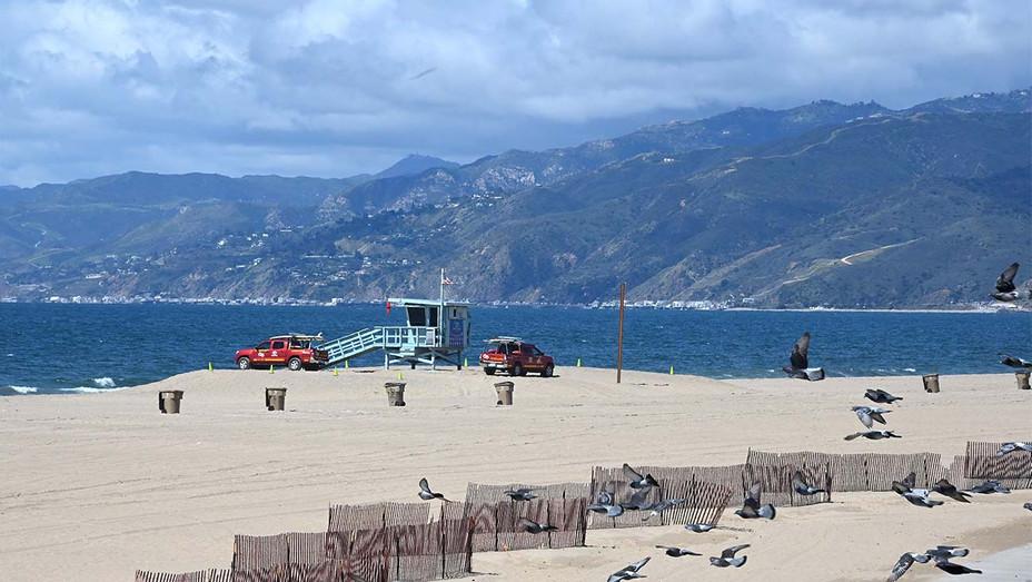 Beach partol trucks are seen on an empty beach in Santa Monica, California - Getty - H 2020