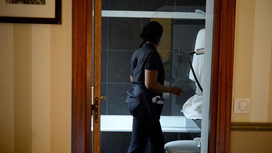 A chambermaid cleans the bathroom - Getty-H 2020