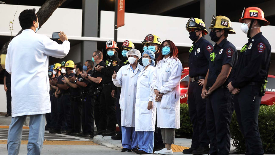 Members of the Glendale police and fire departments pose with healthcare workers as they pay tribute to the healthcare workers   - Getty - H 2020