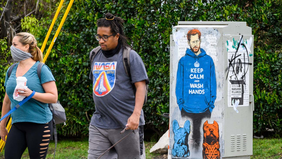 """People walk past graffiti of Prince Harry wearing a hoodie reading """"Keep Calm and Wash Your Hands,"""" on April 7, 2020- Getty - H 2020"""