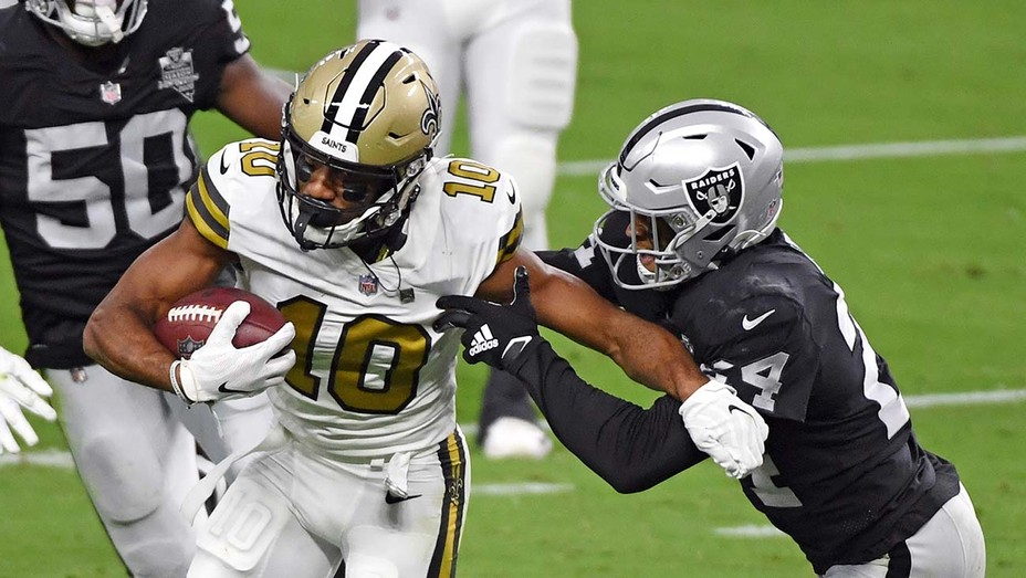 Wide receiver Tre'Quan Smith of the New Orleans Saints avoids a tackle by safety Johnathan Abram of the Las Vegas Raiders.