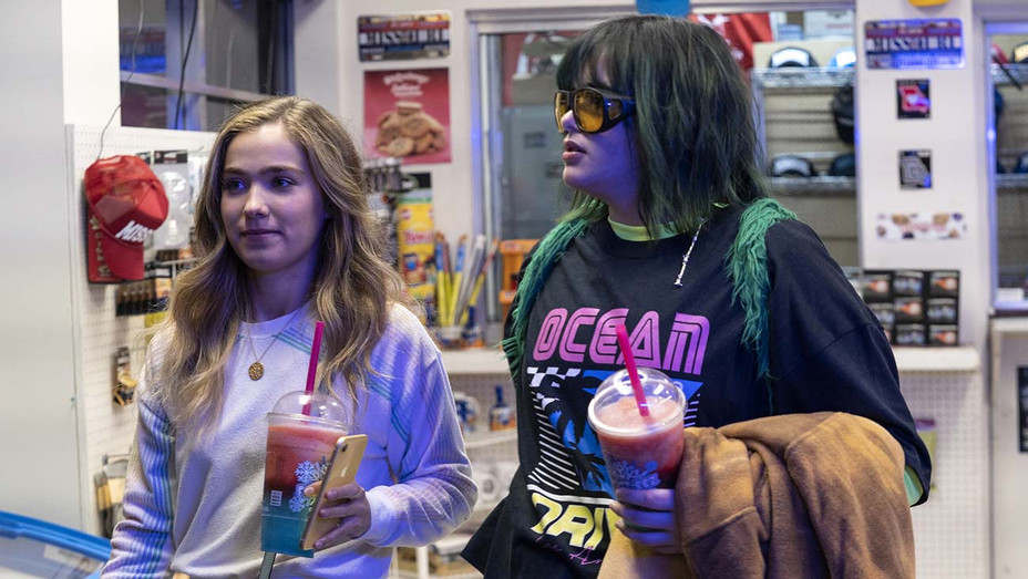 Veronica (left) and Bailey (right) stand at the counter of a convenience store at night, holding large red and blue slushies.