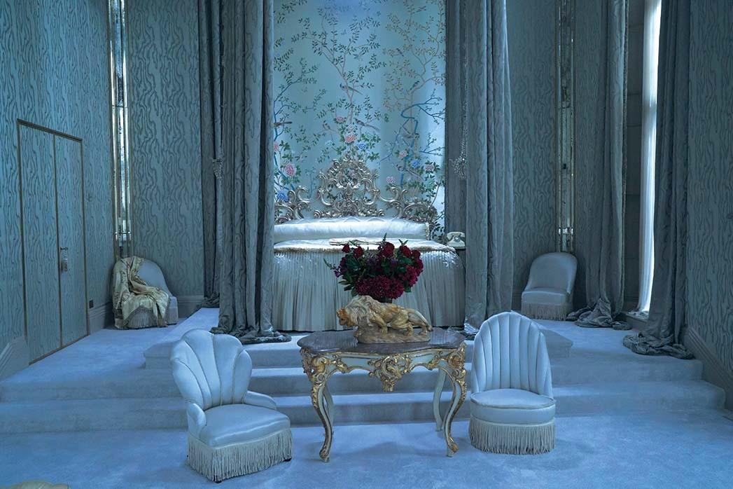 Der Produktionsdesigner wählte eine szenische Tapete der Chinoiserie von de Gournay für das blau- und grau getönte Schlafzimmer, das als eine Art Mausoleum für die verstorbene Rebecca dient.