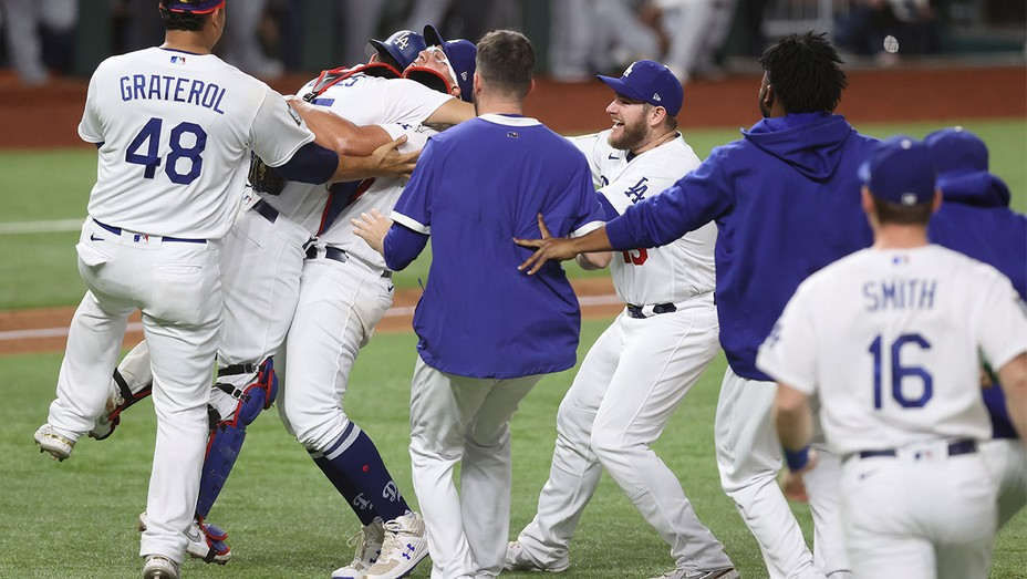 Julio Urias #7 and Austin Barnes #15 of the Los Angeles Dodgers celebrates after defeating the Tampa Bay Rays 3-1 in Game Six to win the 2020 MLB World Series at Globe Life Field on October 27, 2020 in Arlington, Texas.