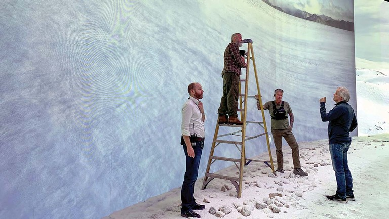 <p>At England's Shepperton Studios, George Clooney (on ladder) surveys one of the giant LED screens depicting vistas shot in Iceland, as (from left) first AD Lee Grumett, grip John Flemming and cinematographer Martin Ruhe look on. </p>
