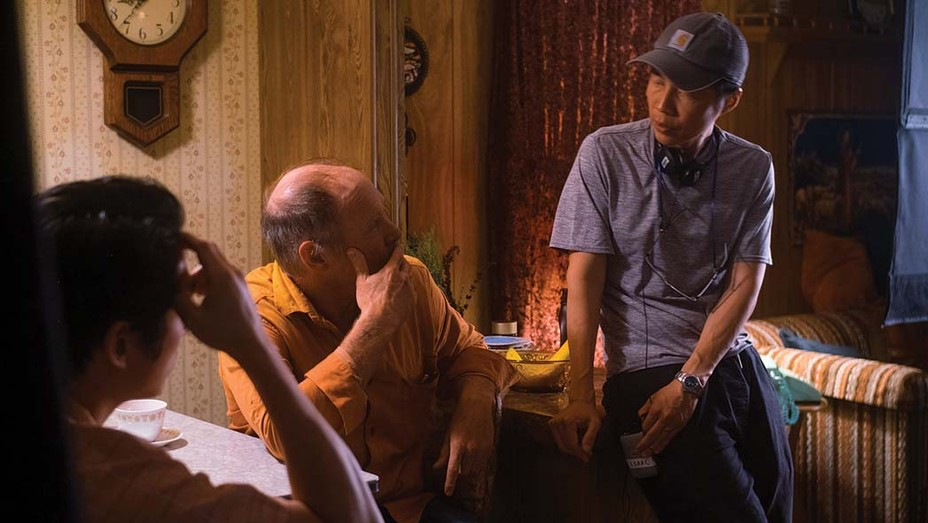 Director Lee Isaac Chung (right) discusses a scene with Will Patton and Yeun. Patton plays a devout Christian whom Yeun hires as a farmhand.