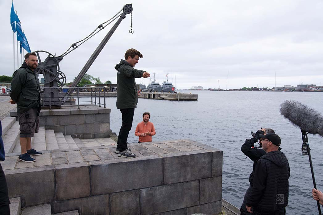 Thomas Vinterberg (center) shot Another Round in the Copenhagen neighborhood where he lives. Here, he lines up a shot for the dance sequence that ends the film.
